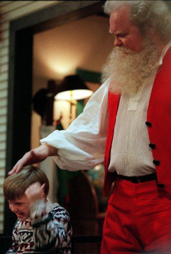 Michael Francingues of the  Schreiber Methodist preschool helps Carl Anderson as Santa Claus  as he participates in story hour at NorthPark Center in Dallas on Dec. 8, 1995.