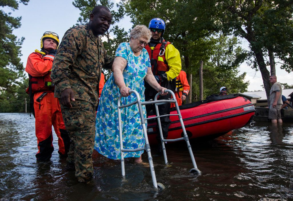 Navy Medic Gayakpa Komi, second from left, helps Sandra Griffin out of a rescue boat as Marines and members of a swift water rescue task force from Tampa, Florida respond to victims of flooding as a result of Tropical Storm Harvey in the Cooks Road area, one of the hardest hit areas in the county, on Thursday, August 31, 2017 near Lumberton, Texas. (Ashley Landis/The Dallas Morning News)
