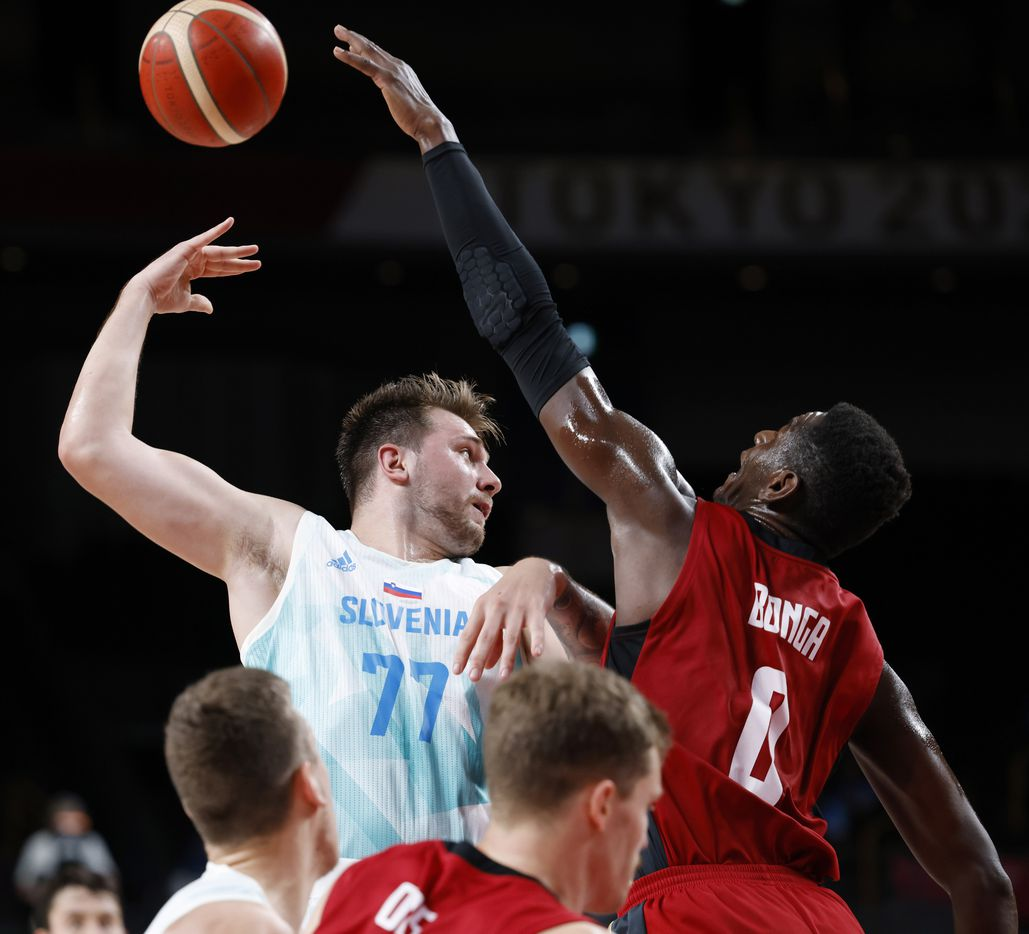 Slovenia's Luka Doncic (77) passes the ball behind his back as he is defended by Germany's Isaac Bonga (0) during the second half of play of a quarter final basketball game at the postponed 2020 Tokyo Olympics at Saitama Super Arena, on Tuesday, August 3, 2021, in Saitama, Japan. (Vernon Bryant/The Dallas Morning News)