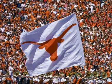 FILE - The Texas Longhorns flag is run across the field after a score during the second half of an NCAA football game against Oklahoma at the Cotton Bowl on Saturday, Oct. 12, 2019, in Dallas.