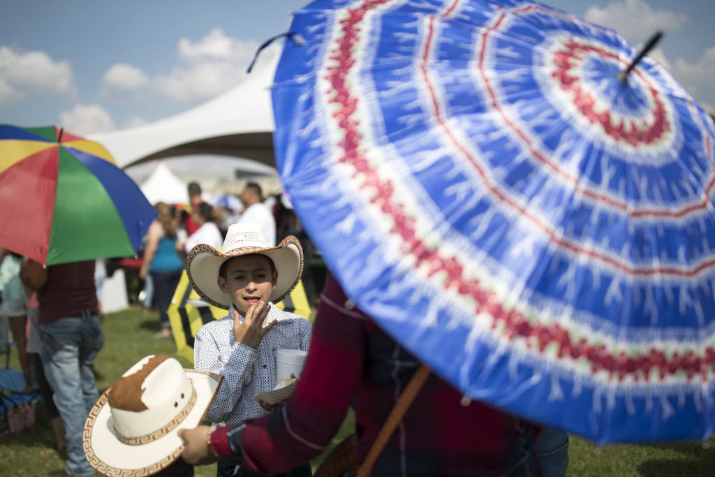 People carrying umbrellas watching performance on stage during La Grande 107.5 Fiestas Patrias at Reunion Park on Sept. 4, 2016 in Dallas.