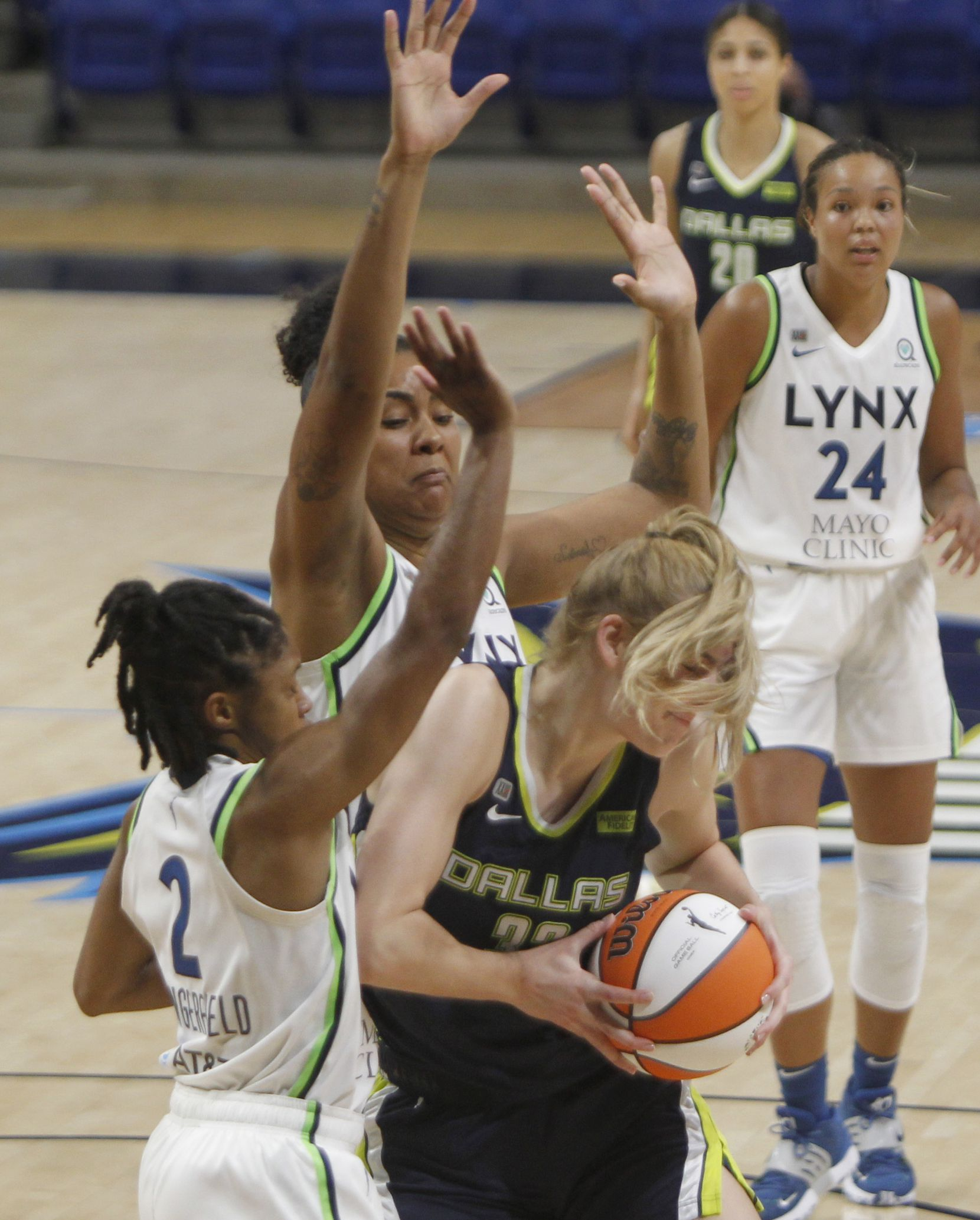 Dallas Wings center Bella Alarie (32) got a face full of her own hair as she drives under the basket against the defense of Minnesota Lynx guard Crystal Dangerfield (2) and Damiris Dantas (12) during 3rd quarter action. The two teams played their WNBA game at College Park Center on the campus of the University of Arlington on June 17, 2021(Steve Hamm/ Special Contributor)