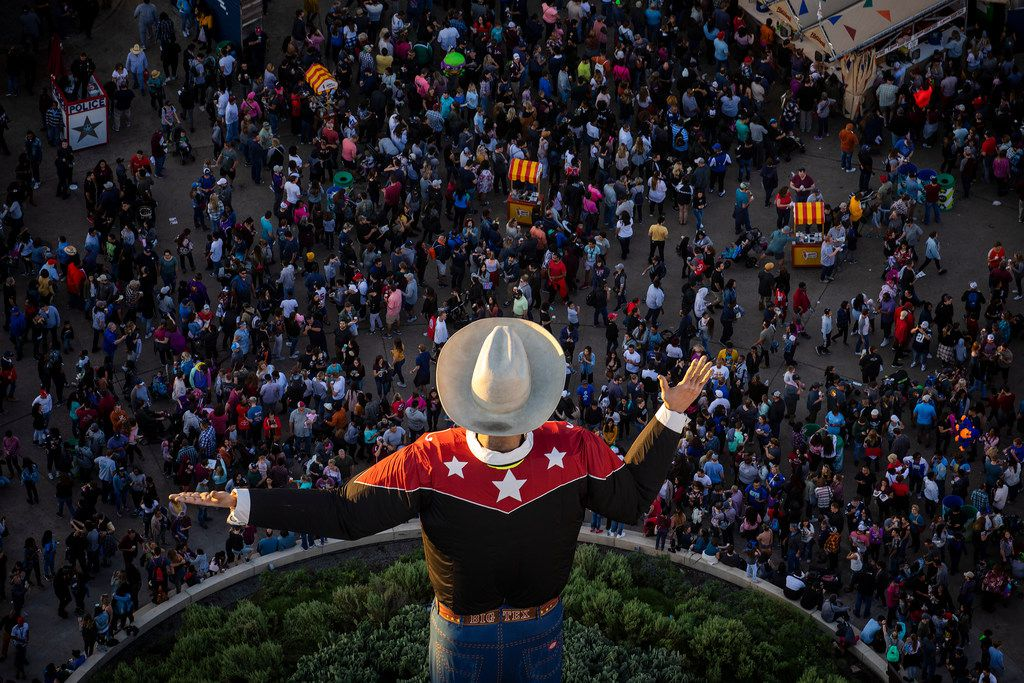 The last rays of sunlight fall over Big Tex as crowds rill the State Fair of Texas in Fair Park on Saturday, Oct. 20, 2018, in Dallas.
