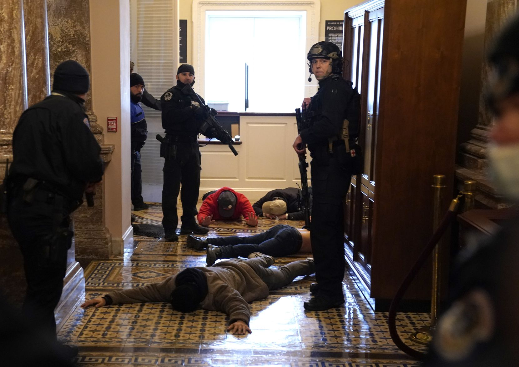 WASHINGTON, DC - JANUARY 06: U.S. Capitol Police stand detain protesters outside of the House Chamber during a joint session of Congress on January 06, 2021 in Washington, DC. Congress held a joint session today to ratify President-elect Joe Biden's 306-232 Electoral College win over President Donald Trump. A group of Republican senators said they would reject the Electoral College votes of several states unless Congress appointed a commission to audit the election results.