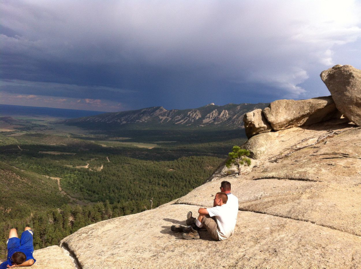 """Tim Barber (center) sits next to his dad, Greg """"Spanky"""" Barber, on a cliff at Philmont Scout Ranch in New Mexico."""