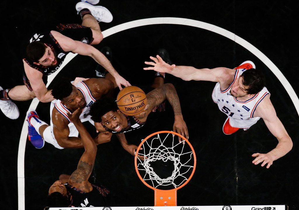 Philadelphia 76ers' Boban Marjanovic, right, shoots over Brooklyn Nets' Ed Davis, center, during the first half in Game 3 of a first-round NBA basketball playoff series Thursday, April 18, 2019, in New York. The 76ers won 131-115. (AP Photo/Frank Franklin II)