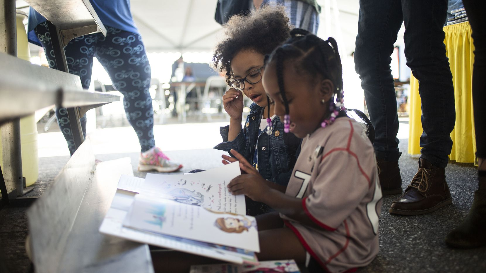 Violet Lewis, 4, left, and her friend Janel Smith, 4, take a moment to flip through a children's book at the Texas Book Festival on Oct. 27, 2018 in Austin, Texas.