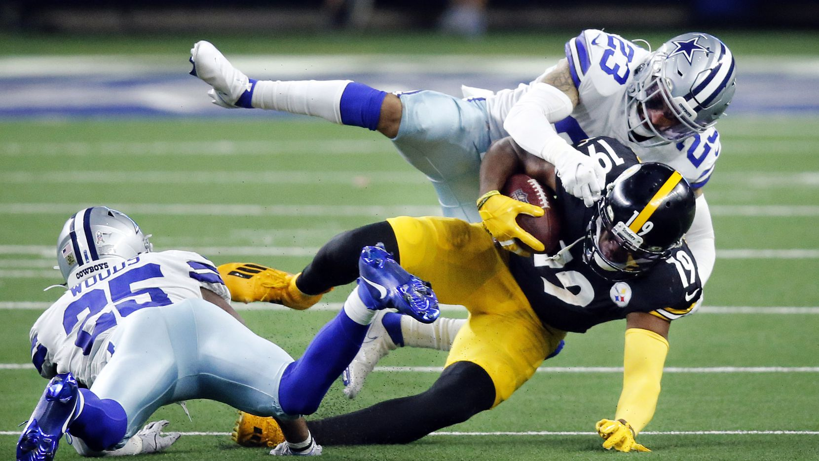 Pittsburgh Steelers wide receiver JuJu Smith-Schuster (19) is taken down by Dallas Cowboys strong safety Darian Thompson (23) and free safety Xavier Woods (25) during the third quarter at AT&T Stadium in Arlington, Texas Sunday, November 8, 2020.