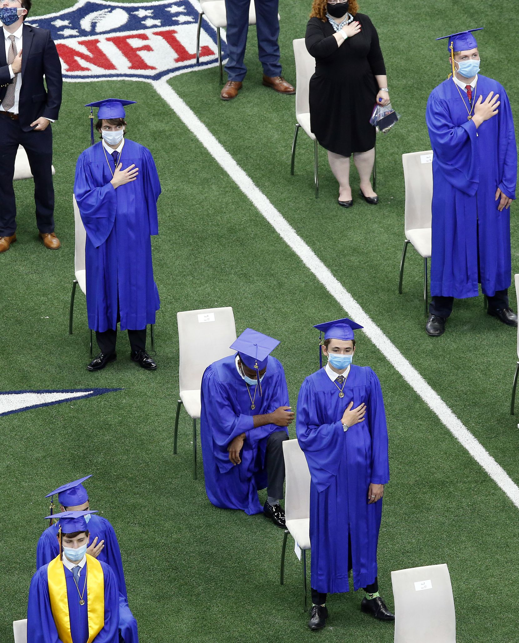 Jesuit College Preparatory School of Dallas graduate Emmitt 'EJ' Smith IV takes a knee during the national anthem at AT&T Stadium in Arlington, Texas, Friday, June 5, 2020. Because of the COVID-19 pandemic, the Dallas Cowboys hosted commencement ceremonies for local schools, including the Arlington ISD high schools. Over 1,100 people were in attendance, to see the 255 graduates get their diplomas.