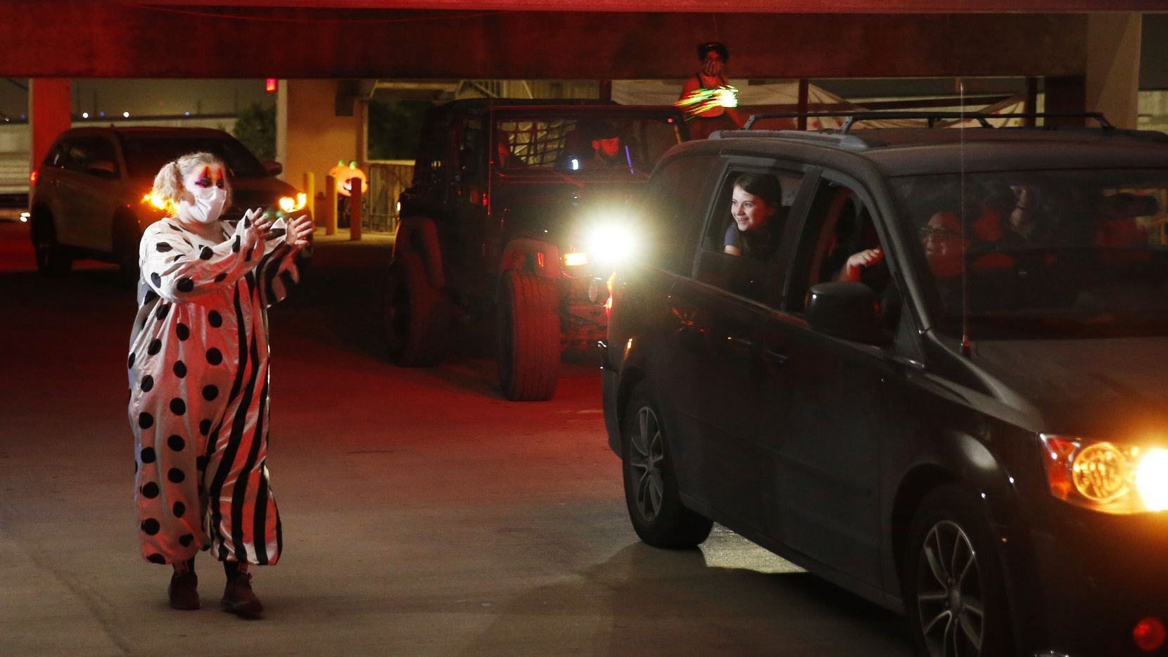 Sarah Jones of Keller, waves to a family as they make their way through the garage during Drive Boo Halloween at American Airlines Center Silver parking garage on Saturday, October 17, 2020 in Dallas. Arlington Public Library will be hosting a similar event aimed at young children.