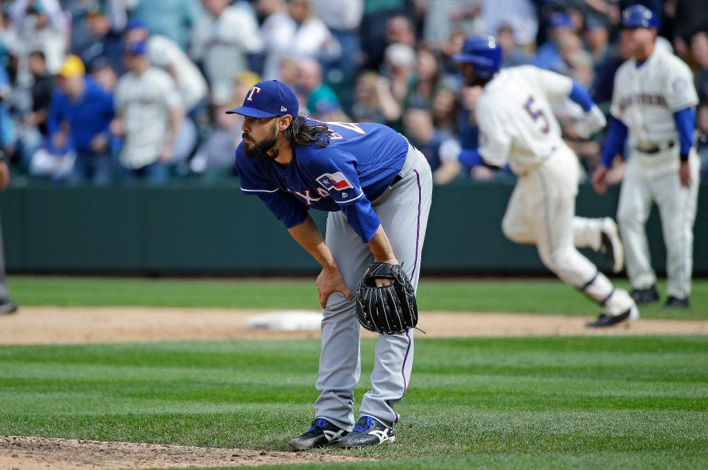 Texas Rangers relief pitcher Tony Barnette reacts on the mound as Seattle Mariners' Guillermo Heredia (5) rounds the bases after Heridia hit a solo home run to tie the baseball game in the seventh inning, Sunday, April 16, 2017, in Seattle. (AP Photo/Ted S. Warren)