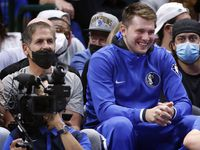 Dallas Mavericks guard Luka Doncic watches the second half from the bench with owner Mark Cuban at the American Airlines Center in Dallas, Wednesday, October 6, 2021.