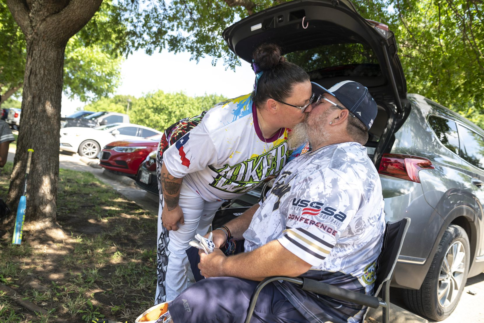 Natasha Reeves gives her husband, Jim Reeves, a kiss before joining a softball game at Kiest Park.