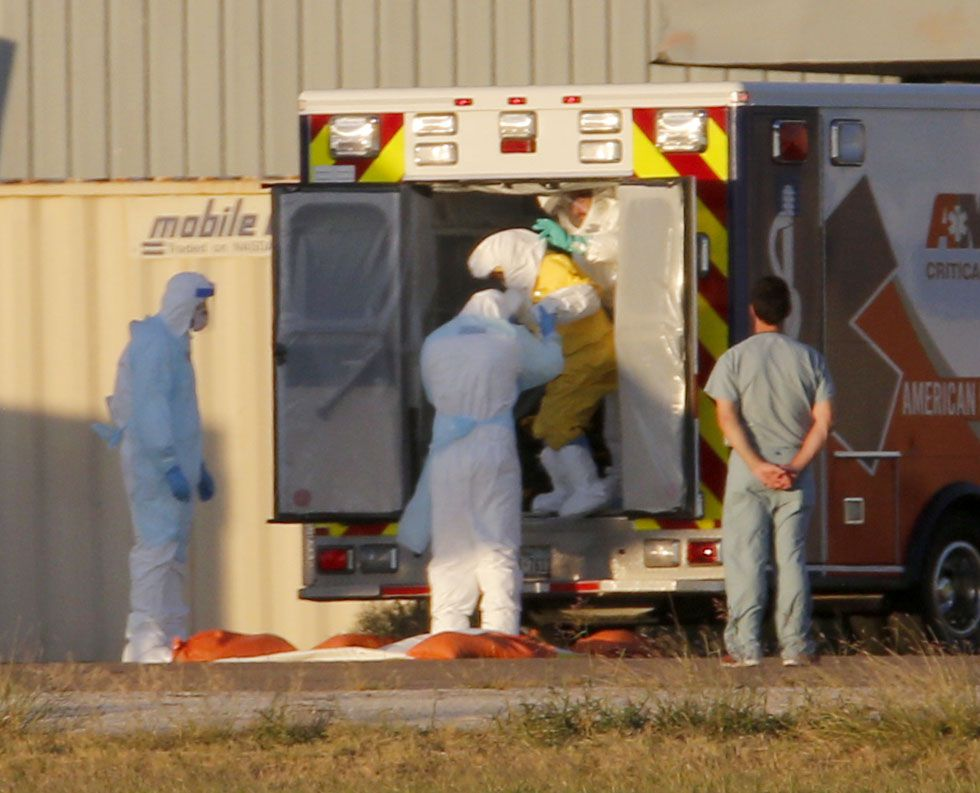 Ebola patient Nina Pham (in yellow) is helped off an ambulance at Dallas Love field for a flight to Maryland and the National Institutes of Health Clinical Center in Bethesda.