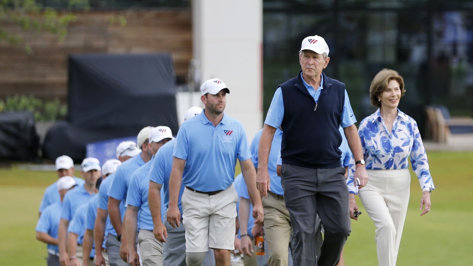 George W. Bush, 43rd President of the United States, walks towards the 18th green with former first lady Laura Bush and veterans before the start of the ceremony during the Warrior Open at the Trinity Forest Golf Club in Dallas.