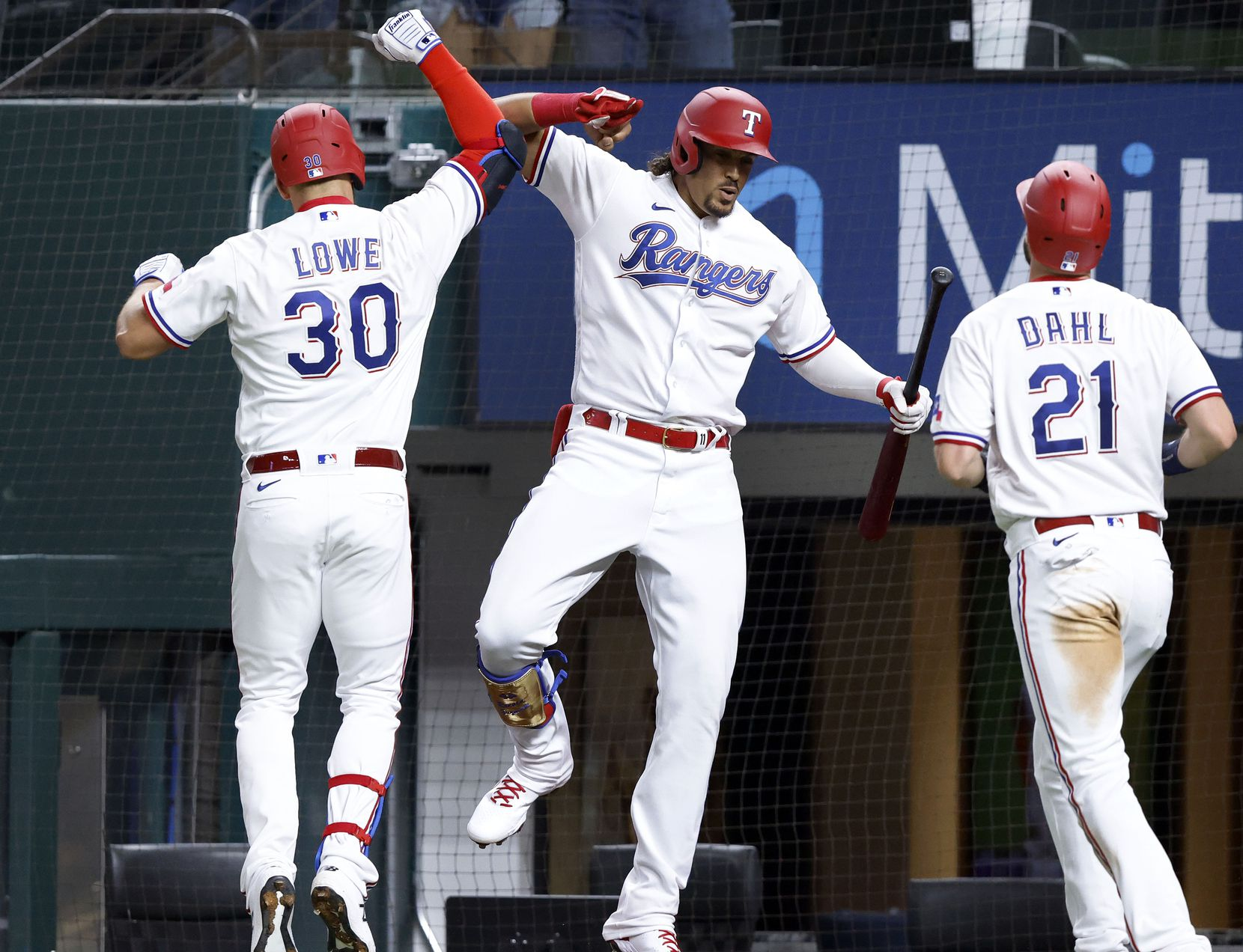 Texas Rangers batter Nate Lowe is congratulated by teammate Ronald Guzman after connecting on a two-run homer during third inning against the Toronto Blue Jays at Globe Life Field in Arlington, Tuesday, April 7, 2021. Lowe scored David Dahl (21). (Tom Fox/The Dallas Morning News)