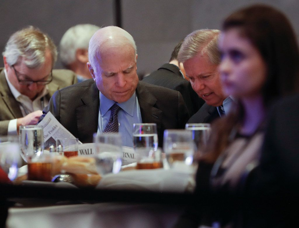 Sen. John McCain, R-Ariz., (left) and Sen. Lindsey Graham, R-S.C., read the Wall Street Journal as they waited for President Donald Trump to speak at the House and Senate GOP lawmakers at the annual policy retreat in Philadelphia on Thursday, Jan. 26. (Pablo Martinez Monsivais/The Associated Press)