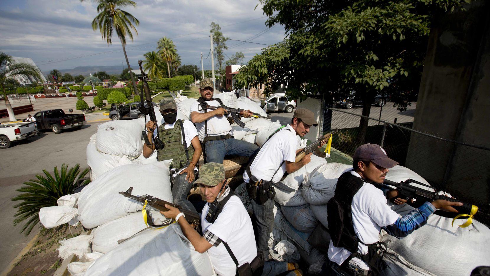 """En esta fotografía de archivo, se ven hombres pertenecientes a grupos de """"Autodefensas"""" en Michoacán patrullando las calles de Nueva Italia, en alerta por la incursión de posibles bandas narcotraficantes."""