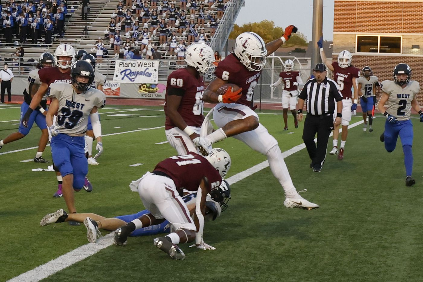 Lewisville's Damien Martinez leaps over a Plano West defender to score a touchdown during the first half of a high school football game in Lewisville, Texas on Friday, Sept. 24, 2021. (Michael Ainsworth/Special Contributor)