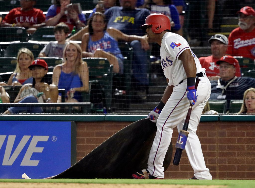 Texas Rangers' Adrian Beltre drags the on deck circle toward himself after being told by tje home plate umpire to get back to the circle during a Nomar Mazara at-bat in the eighth inning of a baseball game against the Miami Marlins on Wednesday, July 26, 2017, in Arlington, Texas. Crew chief Gerry Davis ejected Beltre after that action in the 22-10 Mariners' win. (AP Photo/Tony Gutierrez)