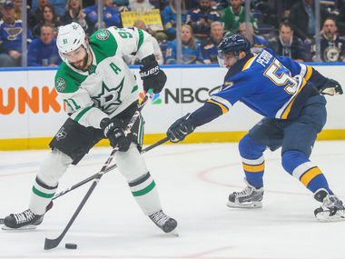 Dallas Stars center Tyler Seguin (91) makes a pass as he is defended by St. Louis Blues defenseman Colton Parayko (55) during Game 1 of an NHL second-round hockey playoff series at Enterprise Center in St. Louis Missouri on Thursday, April 25, 2019.
