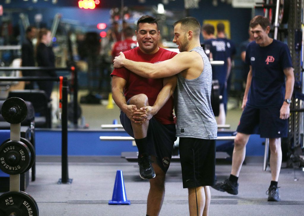 Ryan Bachik, REACT co-founder and program director of tactical operations, helps Addison firefighter/paramedic Steven Martinez at REACT gym in Addison, Texas on Thursday, Jan. 24, 2019. The gym is now offering a free injury prevention training program to Addison first responders. (Rose Baca/Staff Photographer)