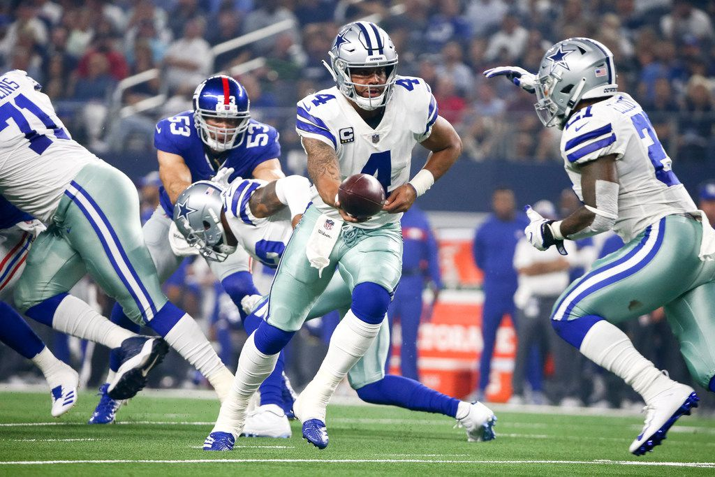 Dallas Cowboys quarterback Dak Prescott (4) hands the ball off to running back Ezekiel Elliott (21) during an NFL game between the Dallas Cowboys and New York Giants on Sunday, September 16, 2018 at AT&T Stadium in Arlington, Texas.