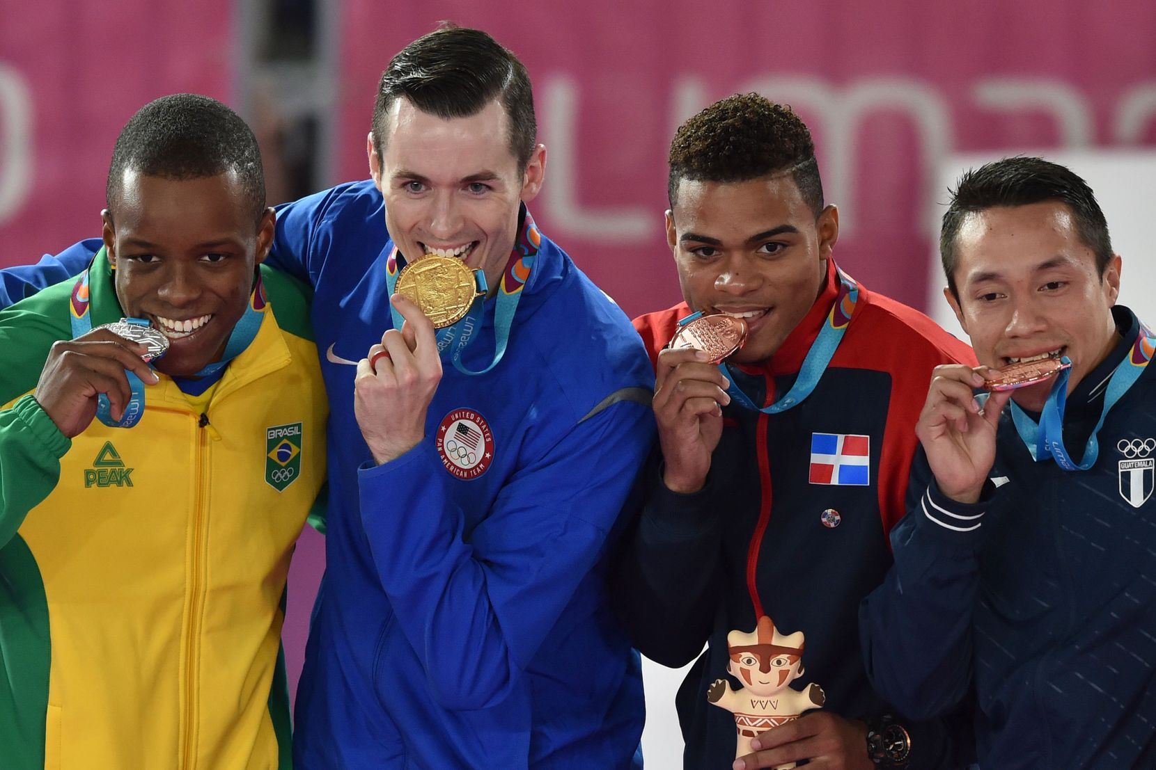 (L to R) Brazil's Verissimo Hernani (silver medal), US Thomas Scott (gold medal), Dominican Republic's Anderson Soriano (bronze medal) and Guatemala's Allan Maldonado (bronze medal) pose during the Pan-American Games Men's Under 75kg Karate awarding ceremony in Lima on August 11, 2019.