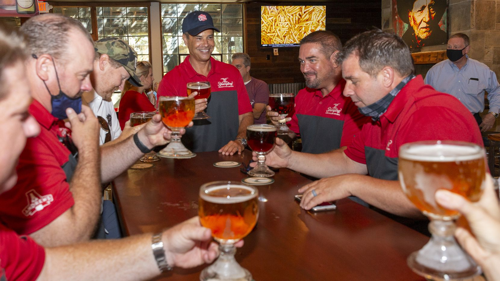 Andrews Distributing CEO Mike McGuire (center) toasts a glass of Yuengling with Andrews Distributing employees at Katy Trail Ice House on Wednesday, Aug. 11, 2021, in Dallas. Katy Trail Ice House is the first establishment to serve Yuengling in Texas. They poured beers bright and early, at 10 a.m.