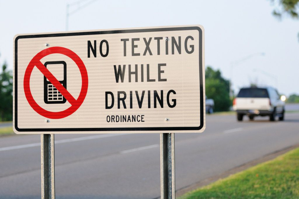 Close up of no texting while driving ordinance sign with vehicle in background.