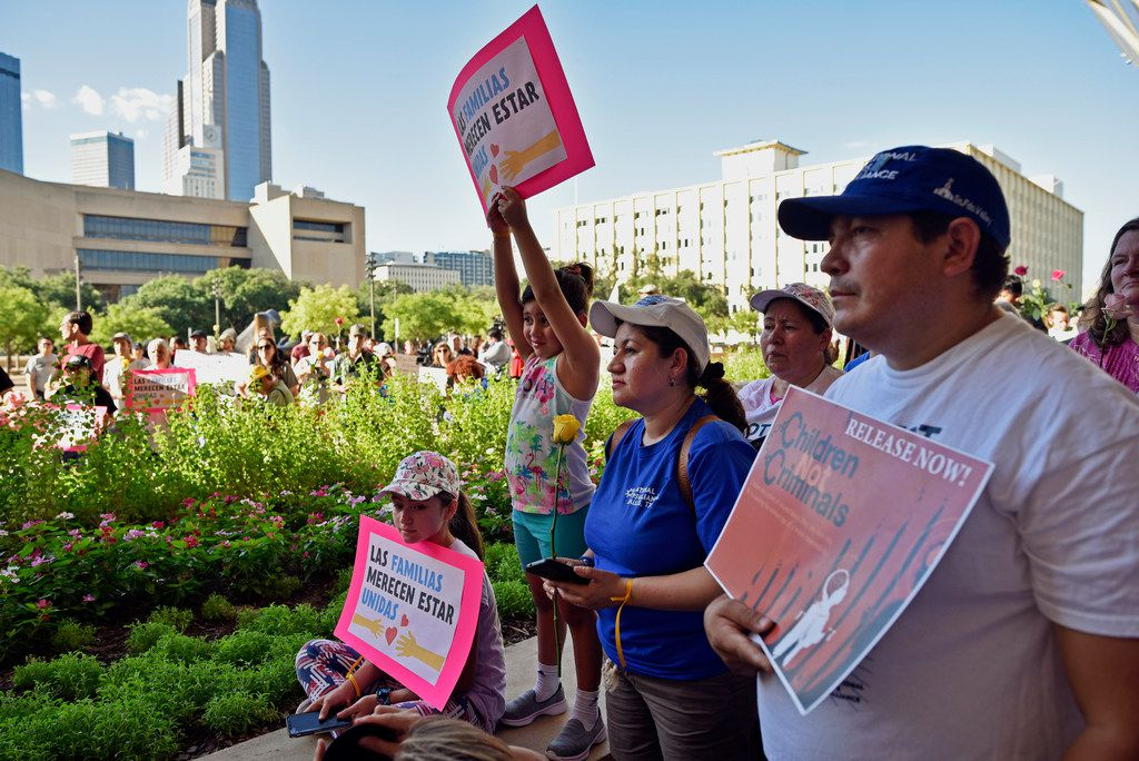 Ariele Rivas, center, 5, holds a sign while standing next to her mother Mili Rivas, center left, and her sister Suri Rivas, 11, during a protest against the U.S. government's border policy, outside of City Hall in Dallas, Thursday, June 14, 2018. The protest was conducted by local activists and the organization Families Belong Together. (Ben Torres/The Dallas Morning News via AP)