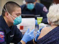 El bombero de Arlington, José Moreno pone una vacuna contra covid-19 de Moderna COVID-19 a una mujer en el Esports Stadium Arlington & Expo Center. En esta ciudad se suspendió la aplicación de la vacuna de Johnson & Johnson.