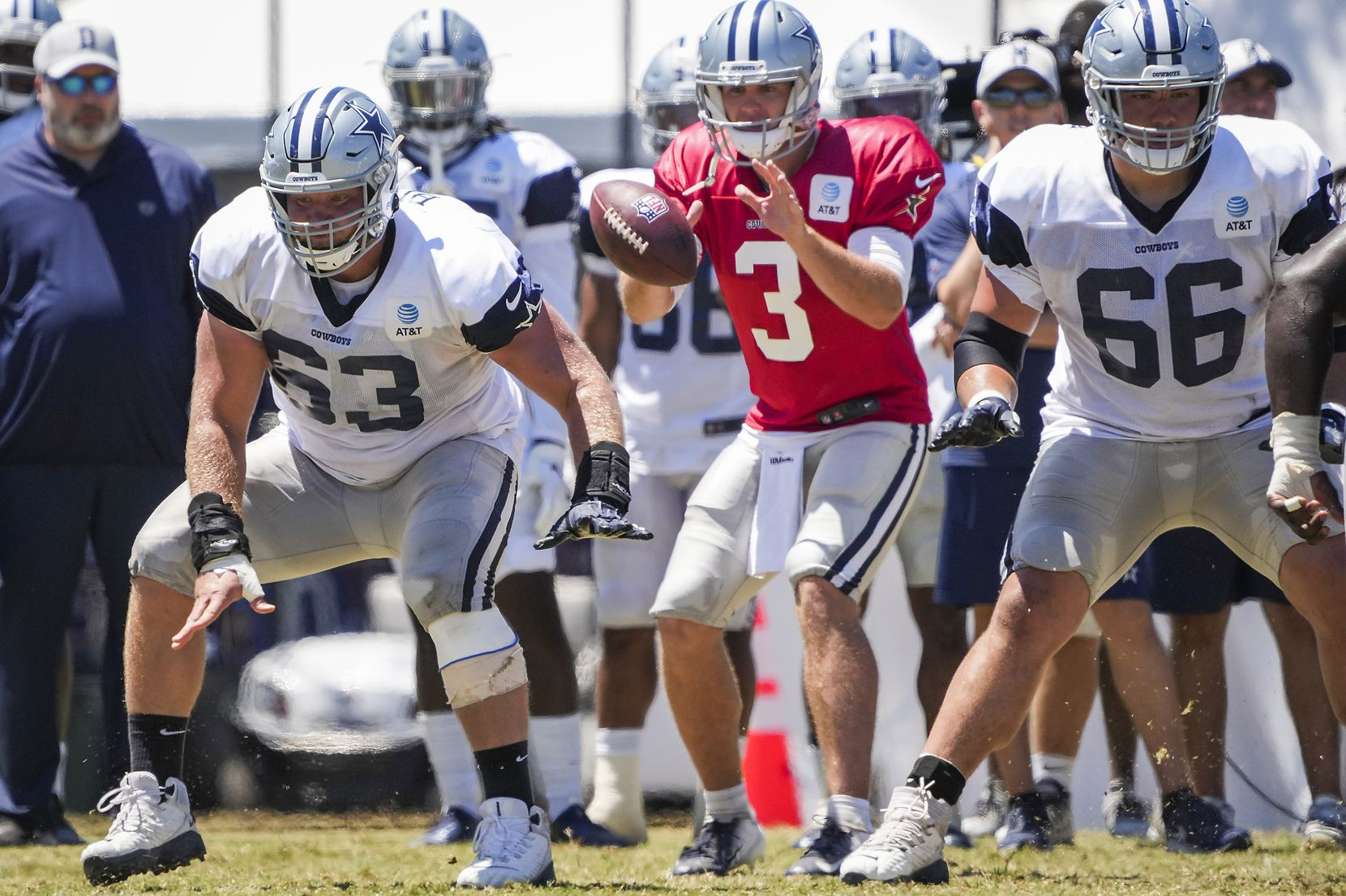 Dallas Cowboys center Tyler Biadasz (63) snaps the ball to quarterback Garrett Gilbert (3) as guard Connor McGovern (66) provides protection during a practice at training camp on Sunday, Aug. 1, 2021, in Oxnard, Calif. (Smiley N. Pool/The Dallas Morning News)