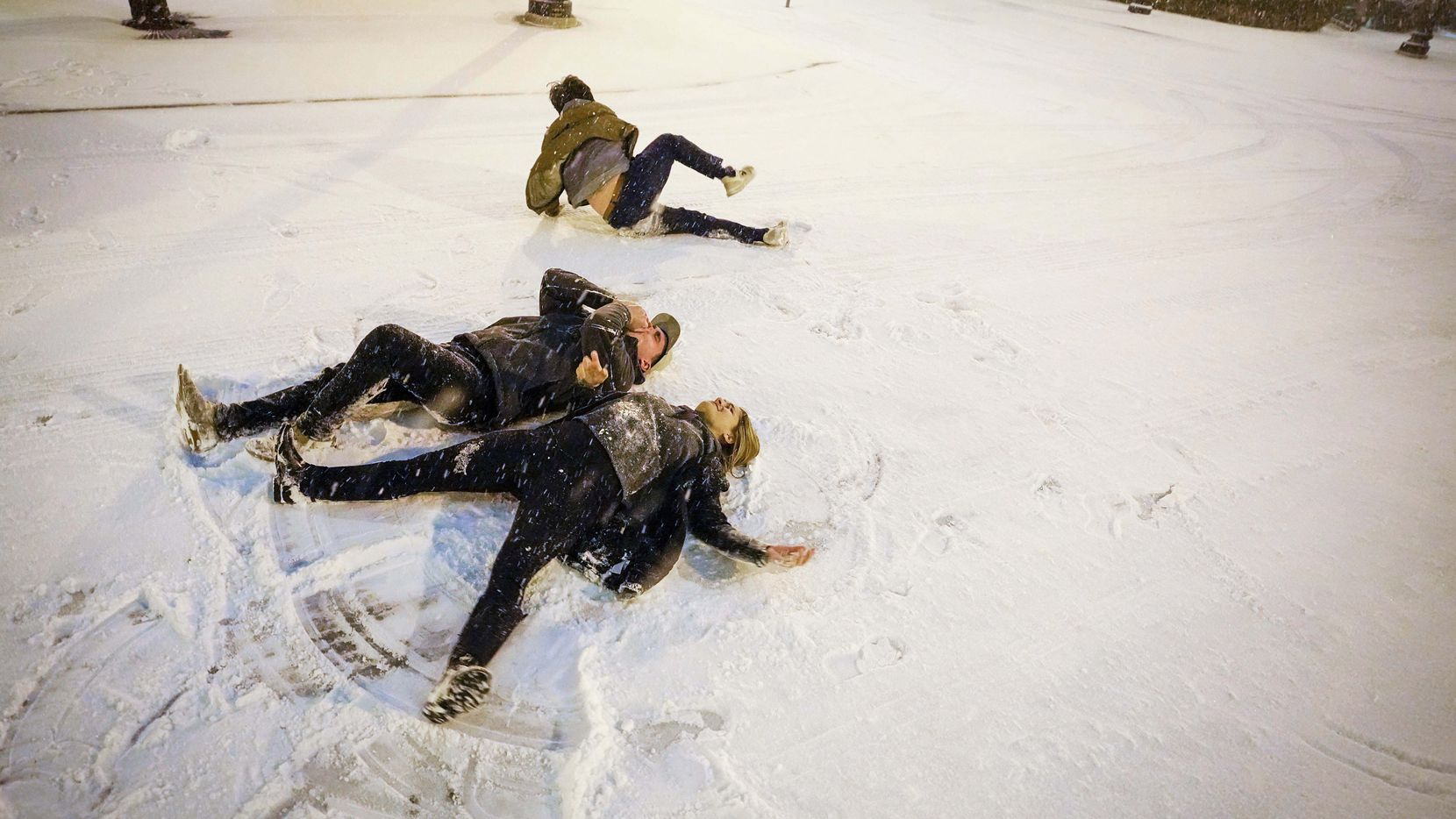 Gabriel Wilke and Gabrielle Rader do snow angles in the middle of Thomas Avenue near Griggs Park as a winter storm brings snow and freezing temperatures to North Texas on Feb. 14, 2021, in Dallas.  A winter storm watch has been issued for all of North Texas, including Dallas, Denton, Collin and Tarrant counties and will be in effect from late Saturday through Monday afternoon.