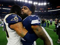 FILE - Todd Gurley (left) congratulates Ezekiel Elliott (center) on the Cowboys' win at AT&T Stadium in Arlington on Sunday, Dec. 15, 2019. The Cowboys beat the LA Rams 44-21.
