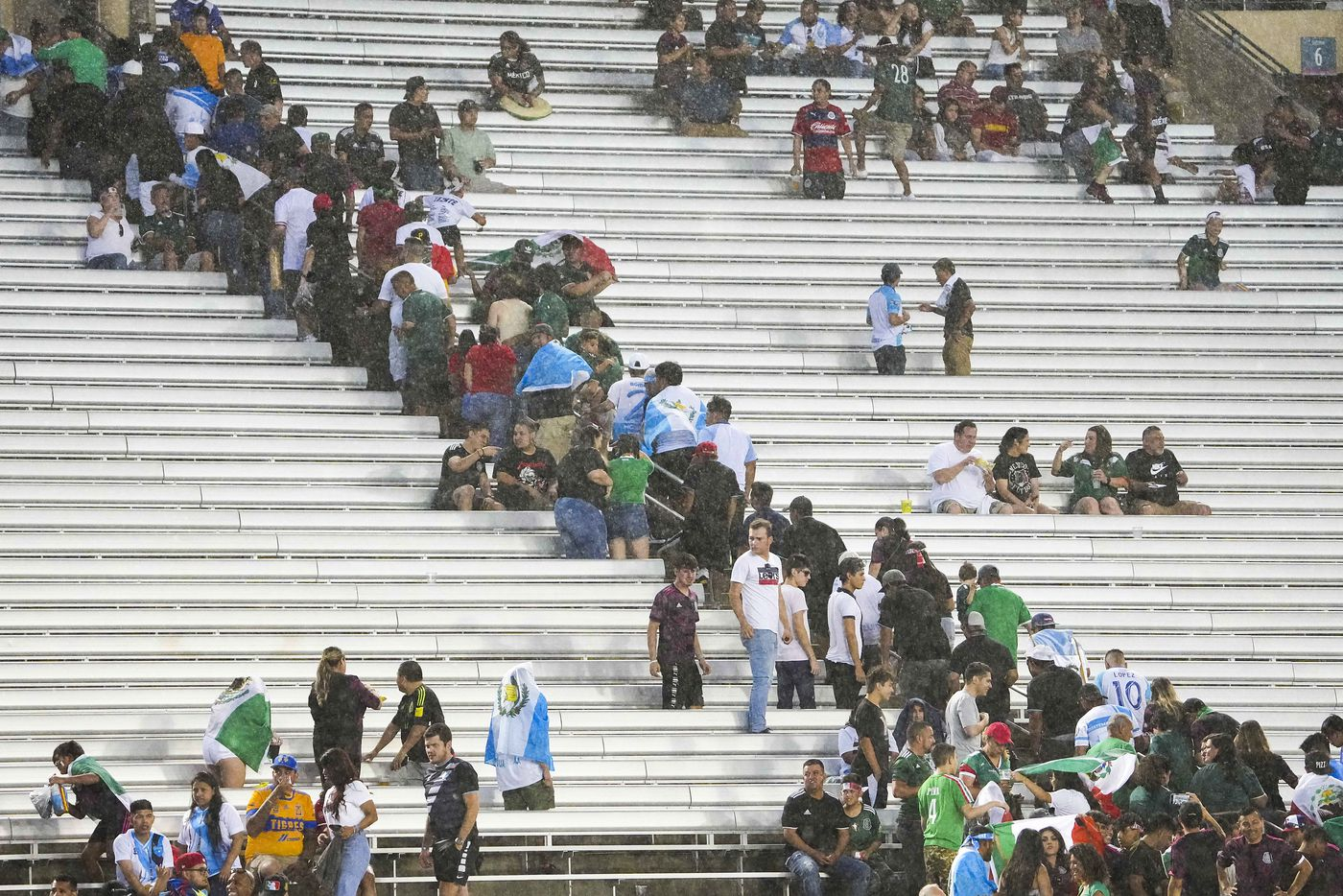 Fans scramble for cover as rain falls on the stadium before a CONCACAF Gold Cup Group A soccer match between the Mexico and the Guatemala at the Cotton Bowl on Wednesday, July 14, 2021, in Dallas. The start of the game was delayed due to weather.