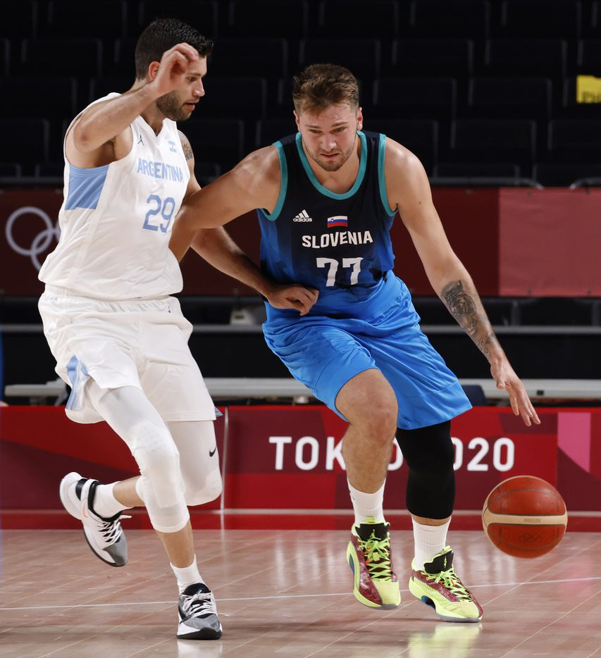Slovenia's Luka Doncic (77) dribbles as he is guarded by Argentina's Patricio Garino (29) during the postponed 2020 Tokyo Olympics at Saitama Super Arena on Monday, July 26, 2021, in Saitama, Japan. Slovenia defeated Argentina 118-100. (Vernon Bryant/The Dallas Morning News)