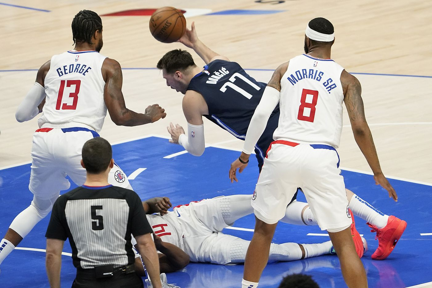 Dallas Mavericks guard Luka Doncic (77) tumbles over LA Clippers guard Terance Mann (14) during the second quarter of an NBA playoff basketball game at American Airlines Center on Friday, May 28, 2021, in Dallas.