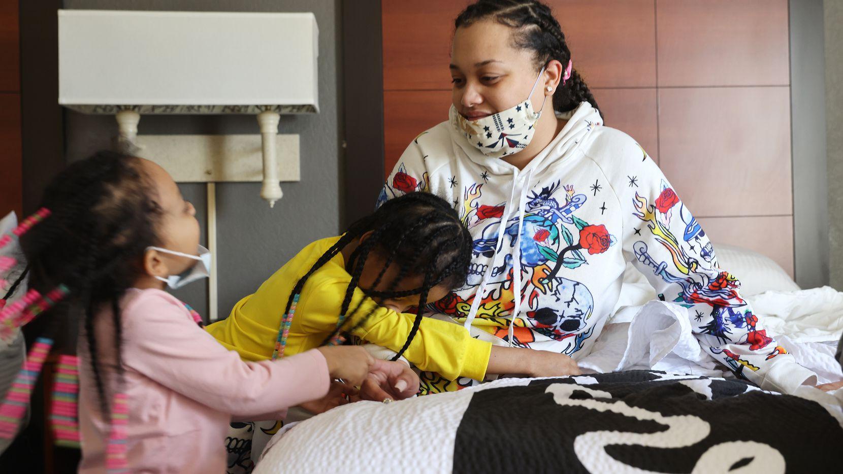 Jonnay Mckinley junto a dos de sus tres sus hijas: Trinity (izq.) y Courtney Young (segunda desde la izq.), al interior de un cuarto de hotel. La familia fue desalojada de su residencia pese a que rige una suspensión de desalojos debido a la pandemia.