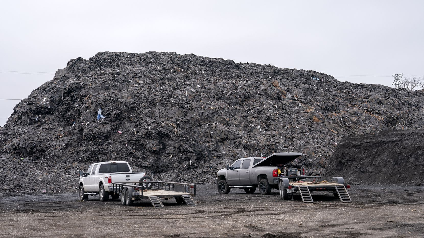Pickups sit next to the pile of roofing shingles known as Shingle Mountain  on Dec. 15, 2020 in southern Dallas.