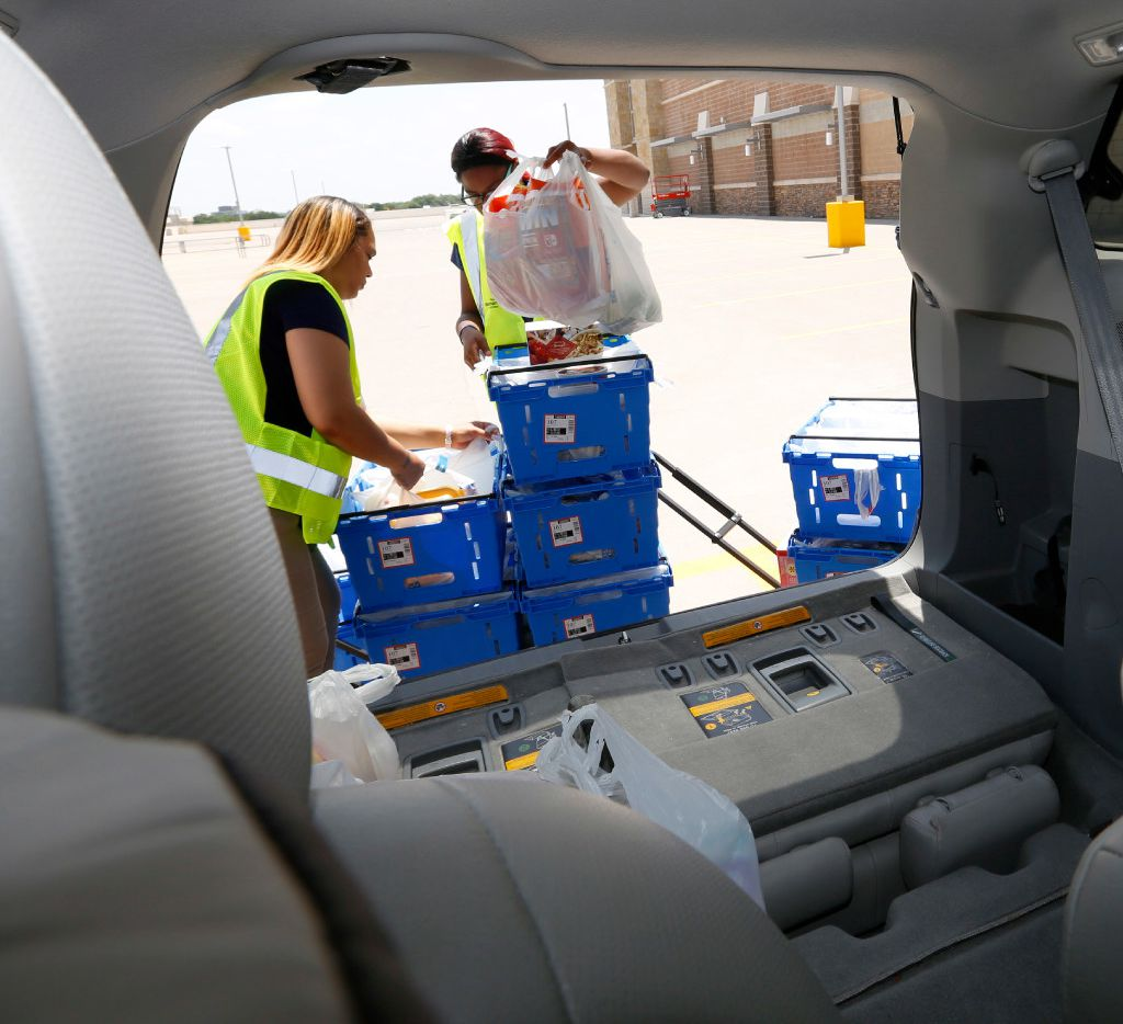 DeTreasure Coker, left, and De Anndria McIntosh place a order in a customer's car at Walmart Supercenter at Timber Creek Crossing in Dallas Friday May 26, 2017. The customer, who has young children, took advantage of Walmart's new online ordering service. (Ron Baselice/The Dallas Morning News)