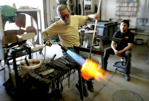 Jim Bowman, left, shapes a piece of molten glass as assistant Alberto Reyes looks on in Bowman's workshop on Griffin Street in April, 2005.