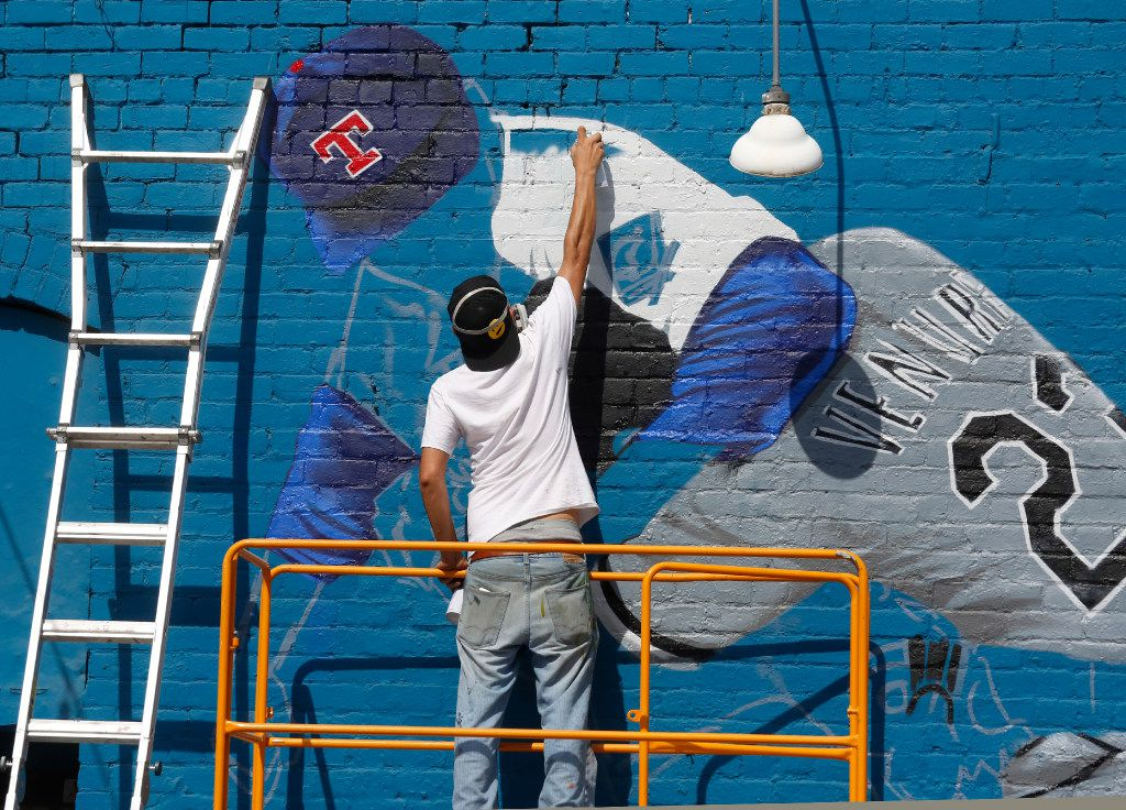 """Dallas-based muralist Isaac """"IZK"""" Davies paints an image of the famous Nolan Ryan punch on the Crowdus St. side of Wits End in Deep Ellum. While painting the mural a neighboring merchant gave the scaffold to Davies. (Ron Baselice/The Dallas Morning News)"""