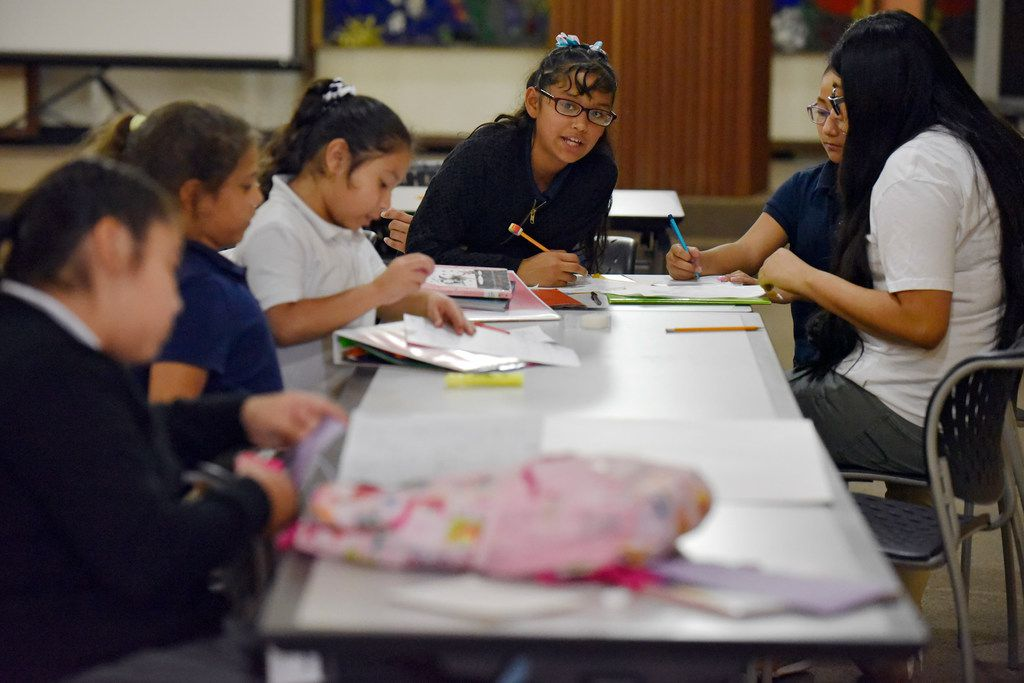 Fourth-graders Angie Zamacona (left) and Hellen Trujillo work on their math homework with tutor Karen Esquivel (far right), during the Trinity River Mission after school program in West Dallas, Monday, Sept. 10, 2018.