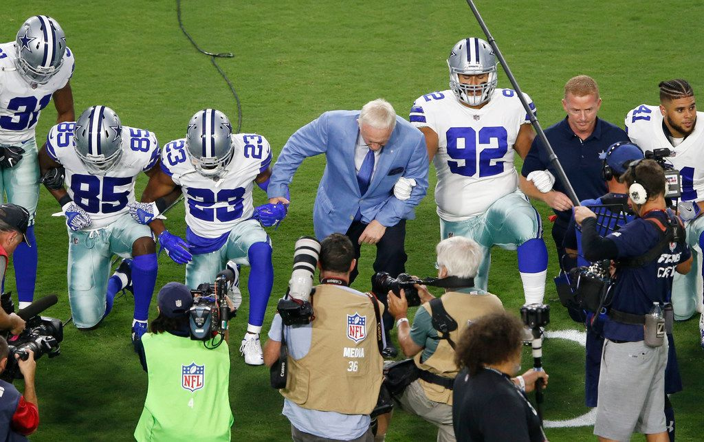 Dallas Cowboys players and staff including owner Jerry Jones and head coach Jason Garrett take a knee before the singing of the National Anthem prior to the start of a game against the Arizona Cardinals at University of Phoenix Stadium in Glendale, Arizona on Monday, September 25, 2017.