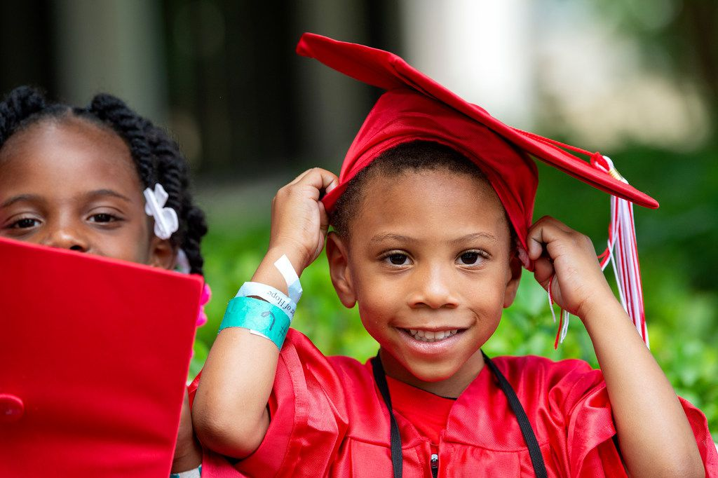 Jerryian, 4, adjust his cap while Zy'Kia, 5, looks on before a graduation ceremony for Kids' University, an educational summer camp put on by Rainbow Days, which serves homeless children, on Friday, June 7, 2019 at the University of Texas at Dallas.