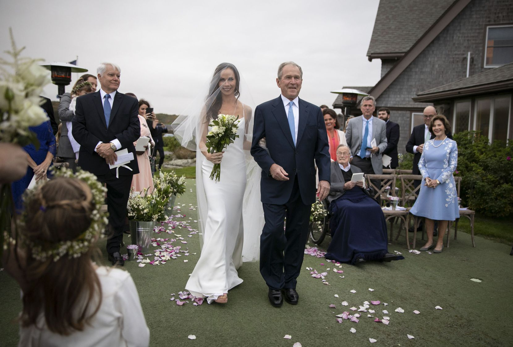 Barbara Bush is walked up the aisle by her father, Pres. George W. Bush, during her wedding to Craig Coyne on October 7, 2018 in Kennebunkport, Maine. With them were Barbara's mother, former first lady Laura Bush, (far right) and her grandfather, former Pres. George H. Bush (seated).