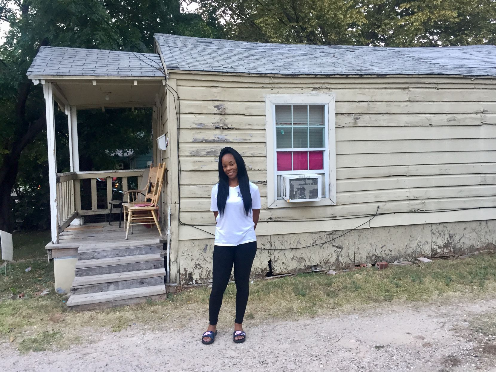 Ashton Elder stands before her newly purchased home. She was an HMK tenant until she bought her 680-square-foot rental in July of this year. (Dianne Solis/The Dallas Morning News)