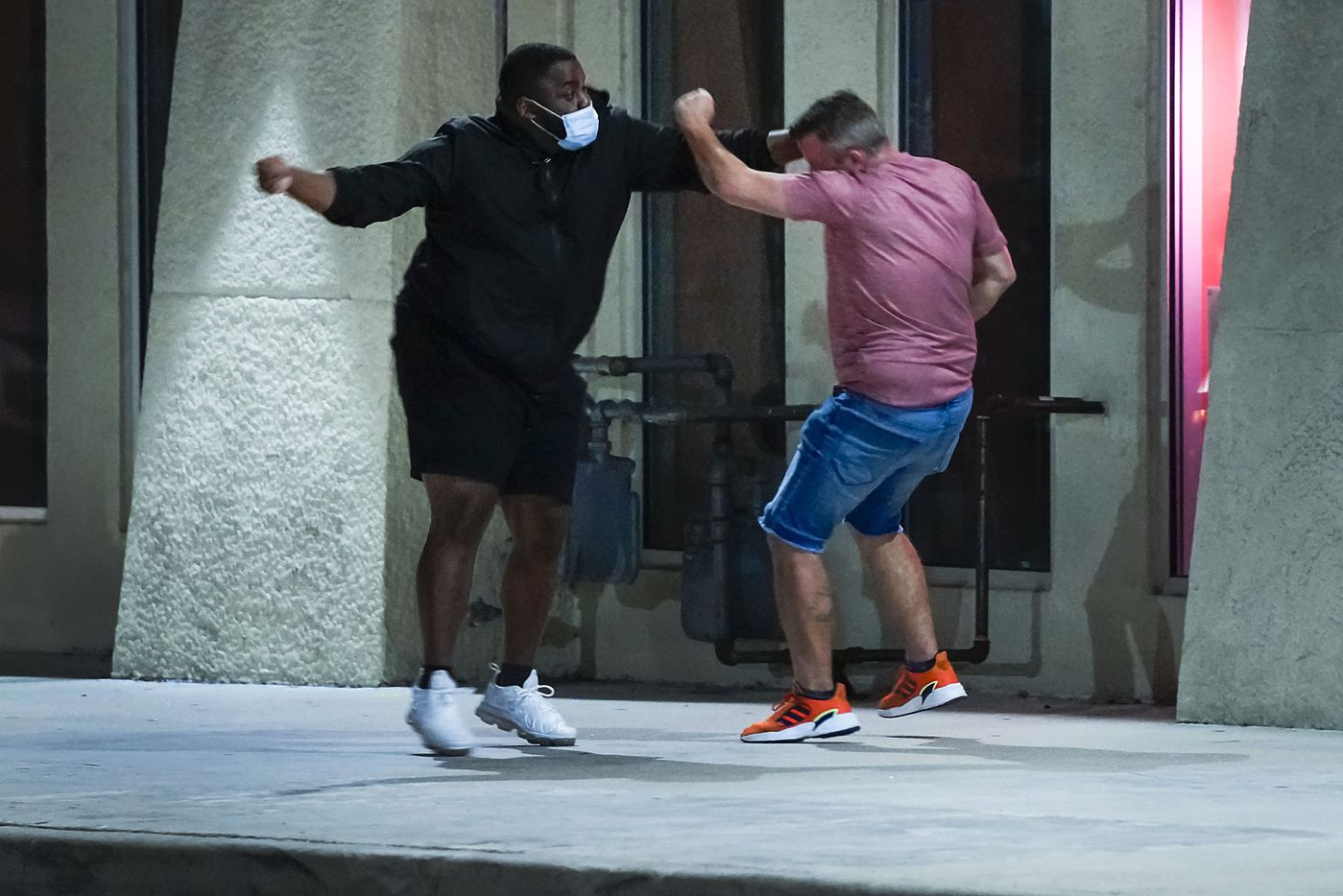 A protester (left) fights with a man who yelled from the sidewalk at marchers near Dallas City Hall on Wednesday, Sept. 23, 2020. After the two argued they briefly scuffled before being separated by other protesters.