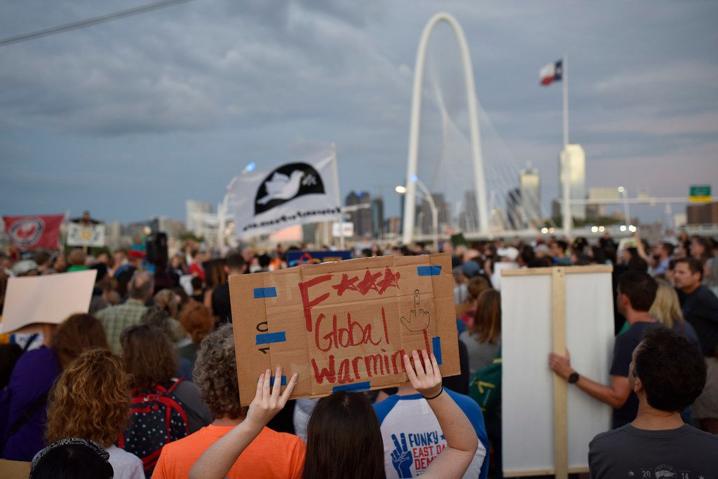 SMU freshman Aden Black, 18, listens to speakers while holding a sign during the Global Climate Strike rally near the Margaret Hunt Hill Bridge in Dallas, Sept. 20, 2019.